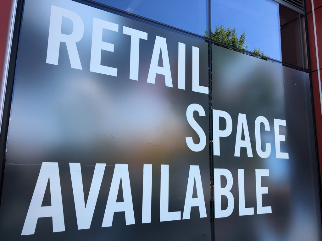CRE rental payments - Retail space available sign in a commercial real estate building